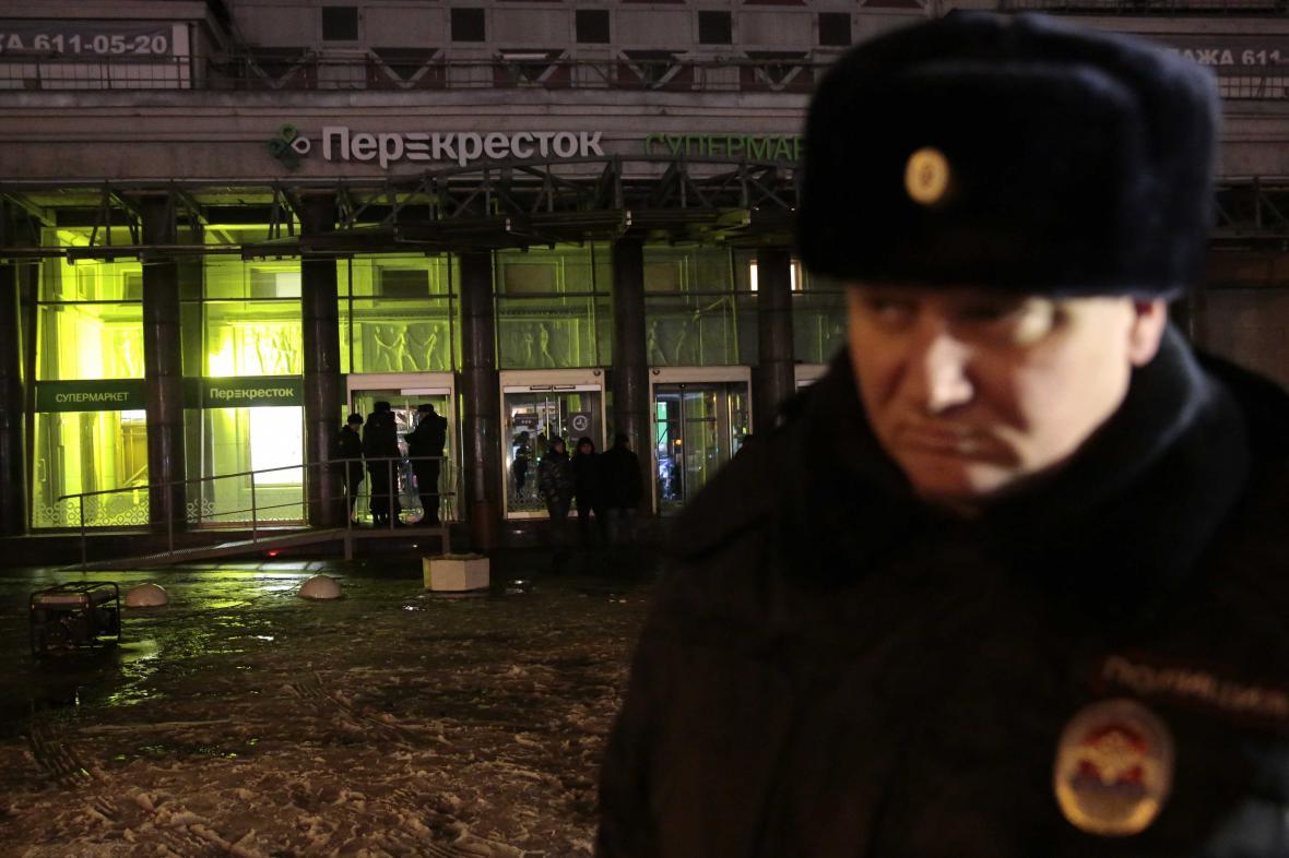 Strážník hlídá místo výbuchu v petrohradském supermarketu