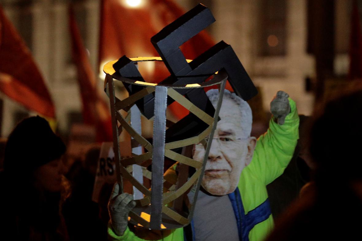 Demonstrant s maskou prezidenta Van der Bellena a s hákovým křížem v odpadkovém koši