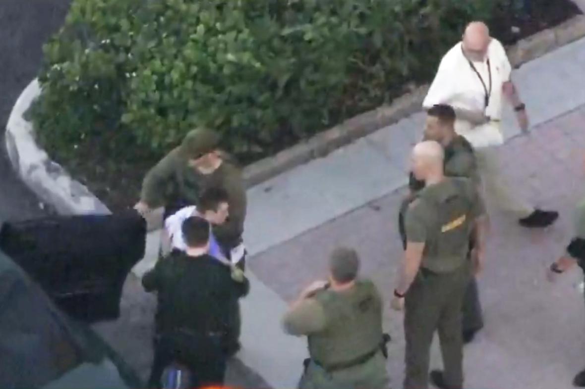 Policie odvádí útočníka z floridského Parklandu