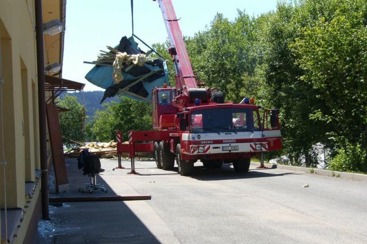 Hasiči pomocí jeřábu odstranili z budovy poničenou střechu