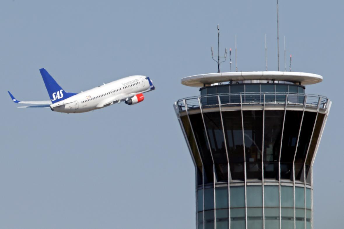 Letadlo SAS letí poblíž řídicí věže letiště Charles de Gaulle v Paříži.