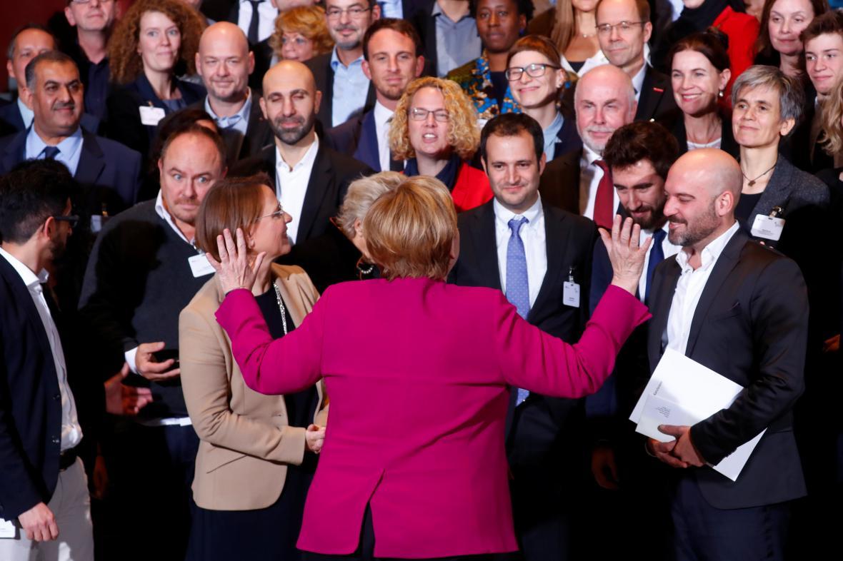Angela Merkelová hovoří k hostům ve svém berlínském sídle