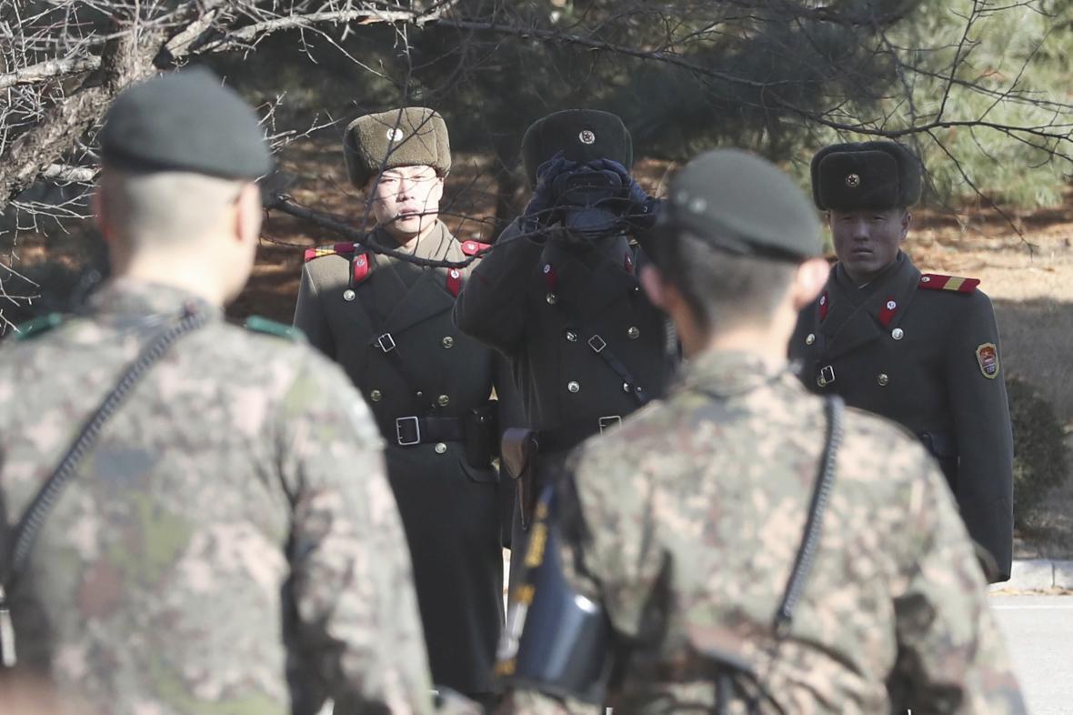 Dva jihokorejští a tři severokorejští vojáci na korejské hranici