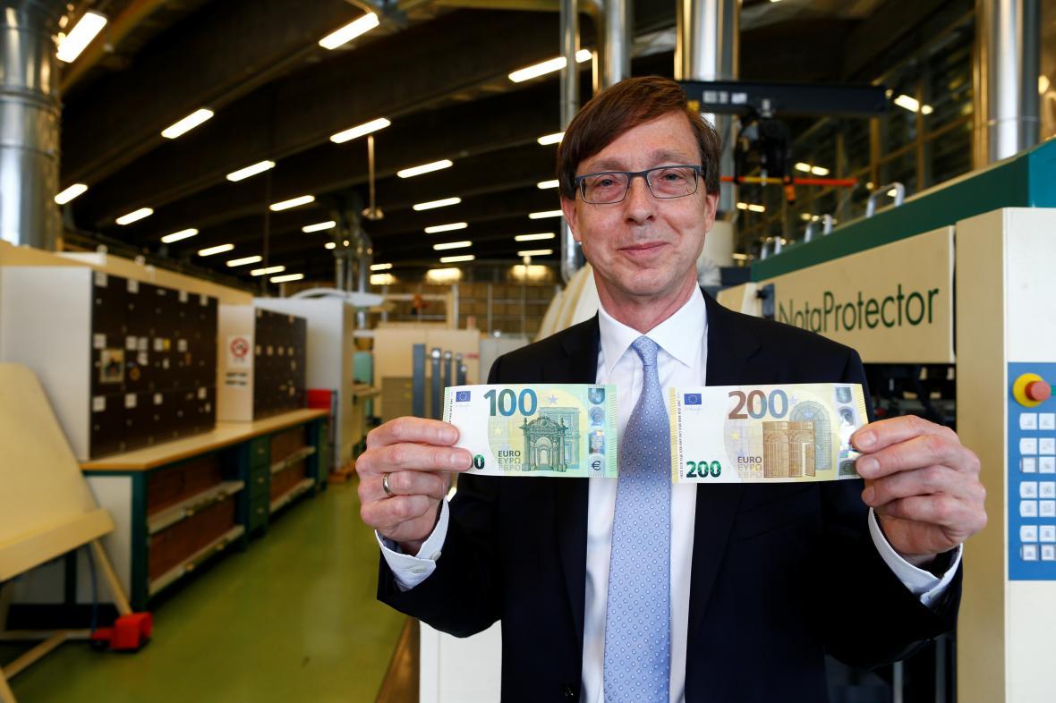 Ton Roos z Evropské centrální banky ukazuje v tajném trezoru nové bankovky v hodnotě 100 a 200 eur.
