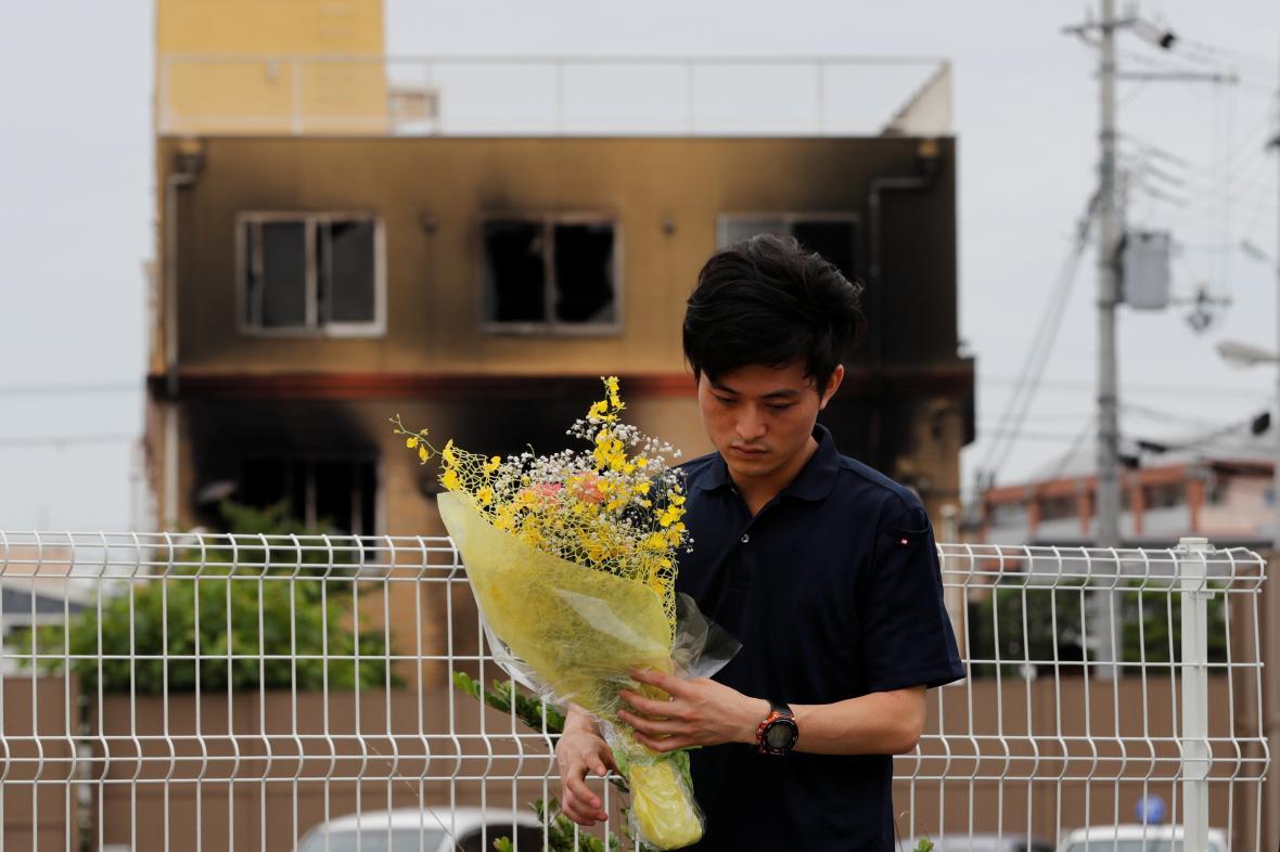 Muž přinesl kytici k uctění obětí požáru studia animovaného filmu v Kjótu