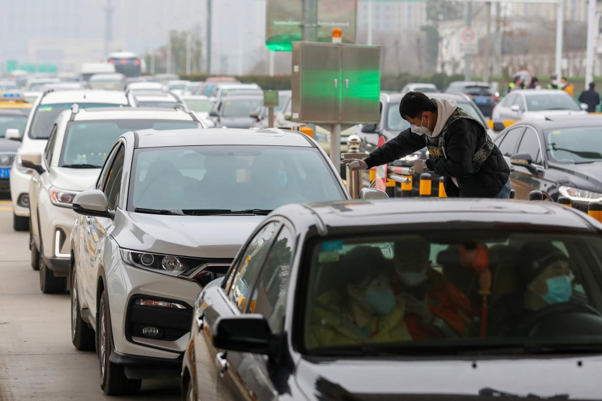 Člen týmu, který má na starosti prevenci, měří teplotu lidem v autech