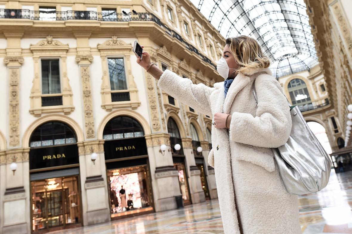 Žena s ochrannou maskou se fotí ve vylidněném centru Milána
