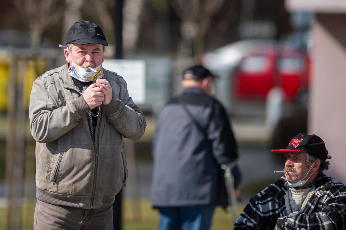 Muž s rouškou si zapaluje cigaretu