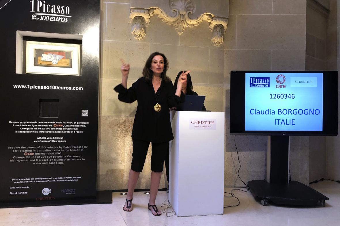 Moderátorka Peri Cochinová gestikuluje, zatímco jméno vítězkyně se objevilo na obrazovce v Paříži