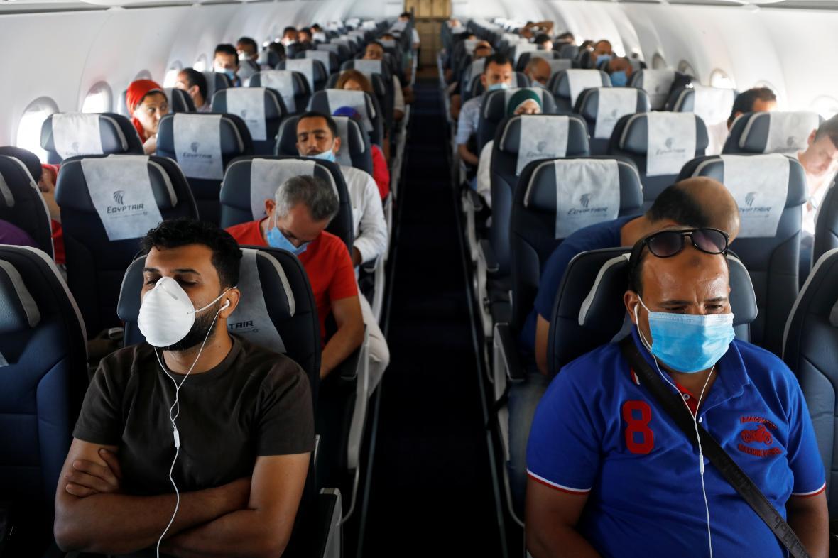 Cestující v letadle v průběhu koronavirové pandemie