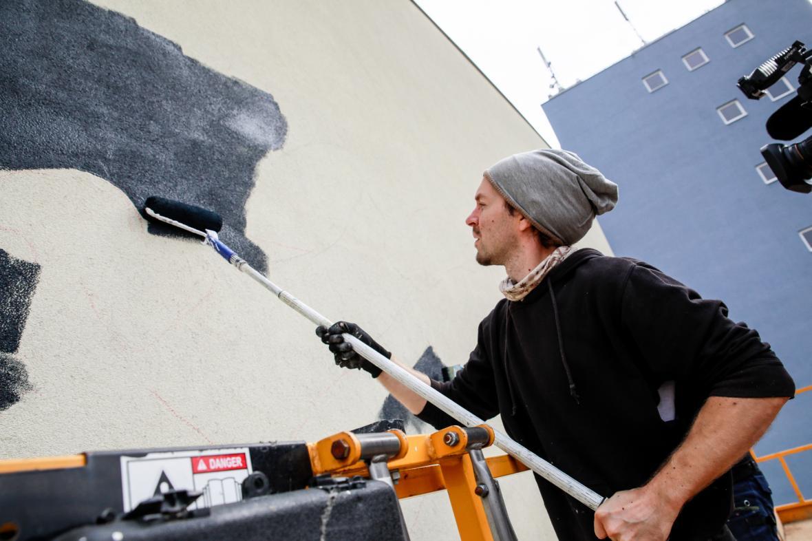 Výtvarník Lukáš Veselý vytváří malbu na domě