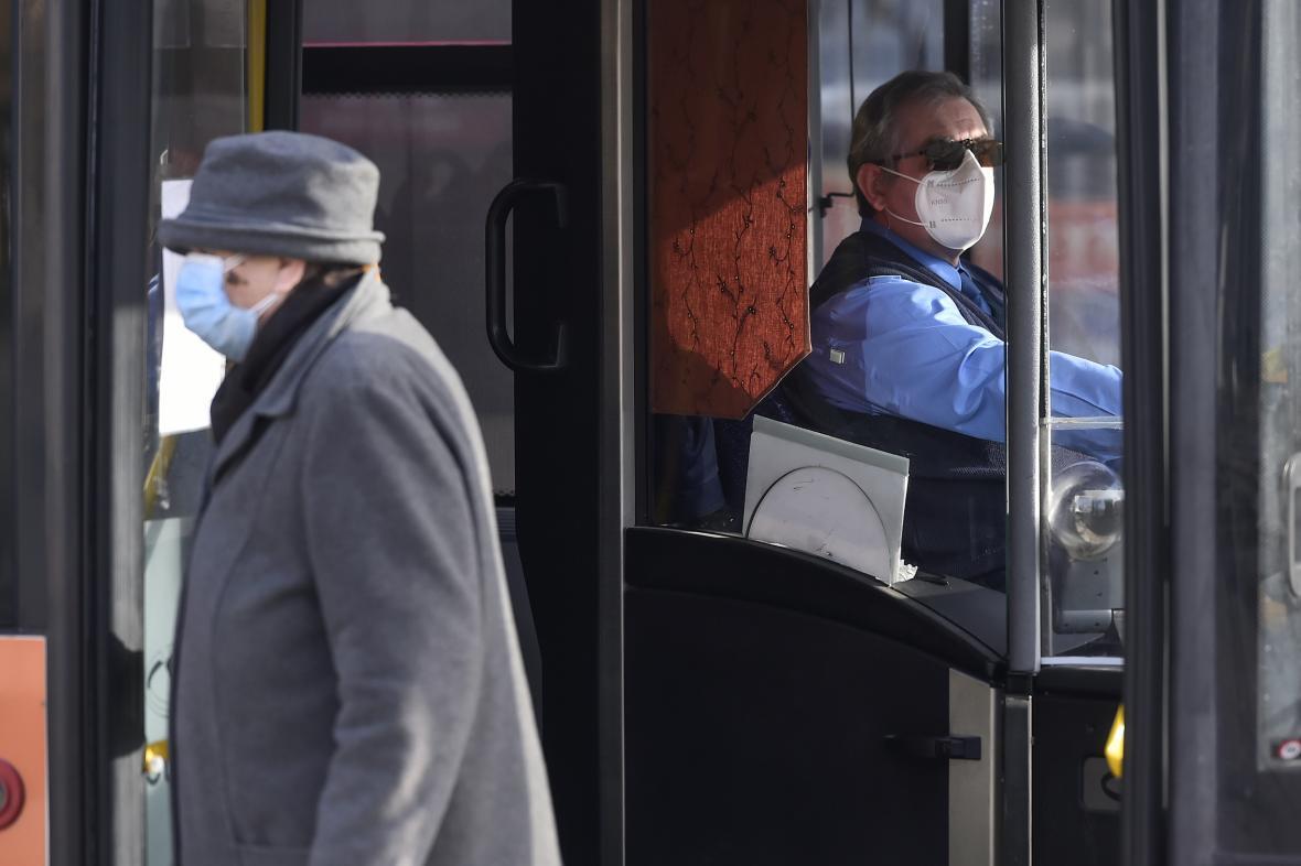 Žena venku s chirurgickou rouškou, řidič hromadné dopravy v respirátoru