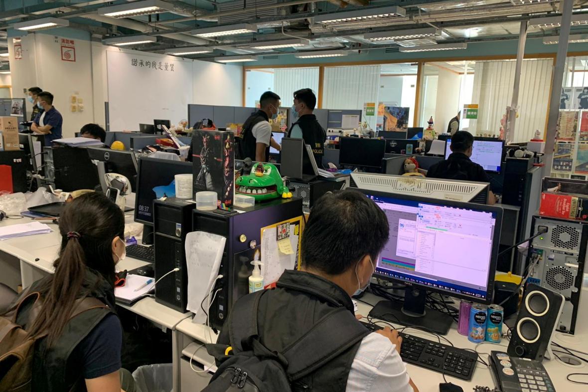 Policisté prohlížejí počítače v redakci deníku Apple Daily
