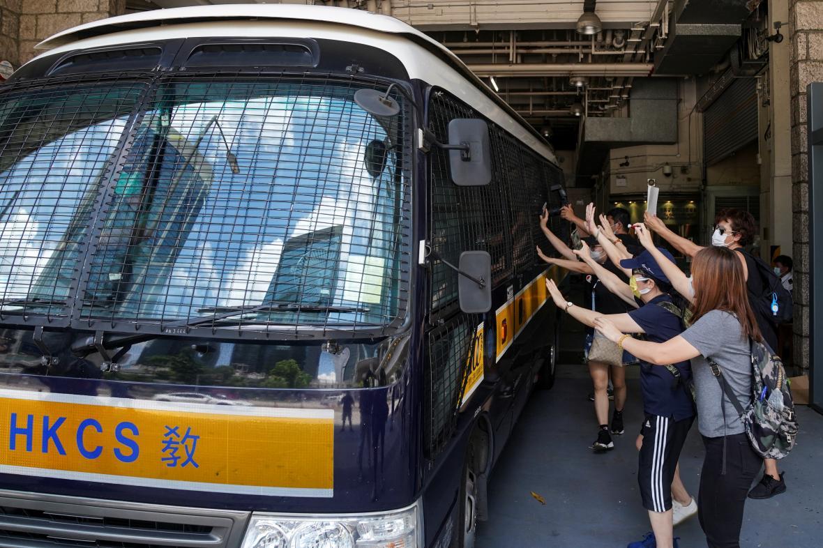 Podporovatelé Tong Ying Kita mávají na vůz, který ho transportuje do vězení