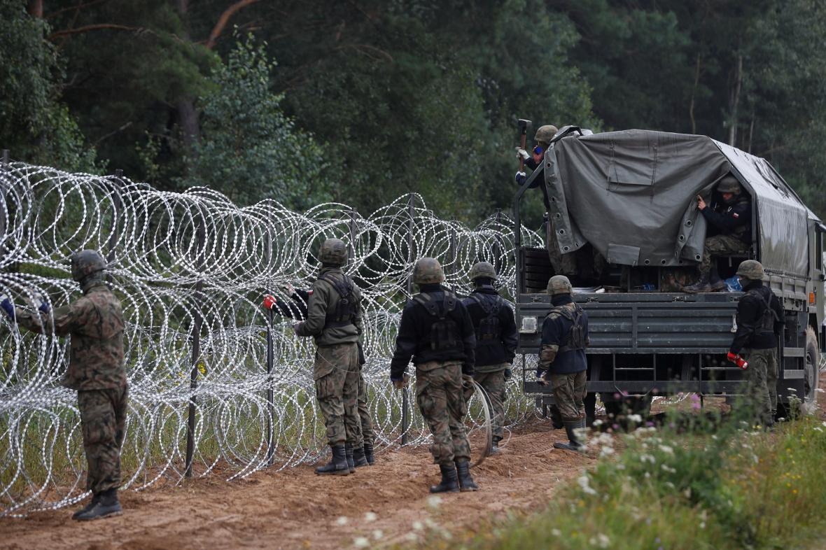 Polsští vojáci staví plot na hranici s Běloruskem