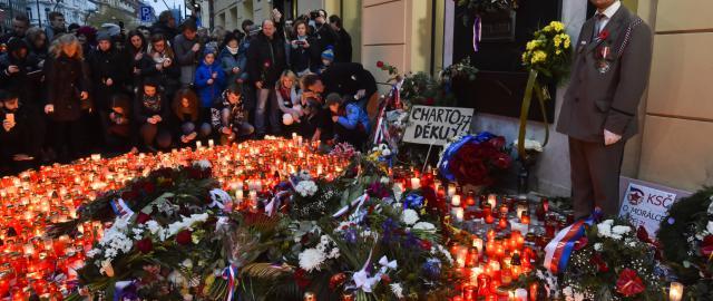 Lidé přicházeli zapálit svíčky a položit kytice k pamětní desce na pražské Národní třídě