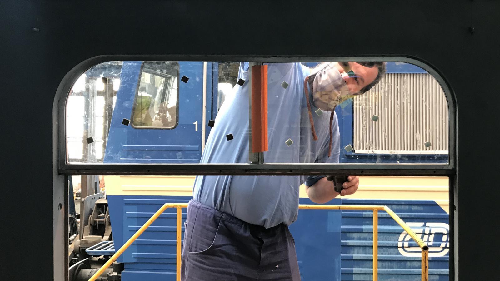 Dělník opravuje okna železničního vozu, budou mít dřevěné rámy