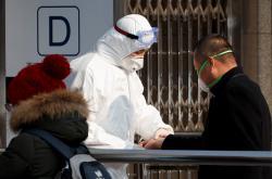 Cestující procházejí v Pekingu zdravotní kontrolou před vstupem do metra