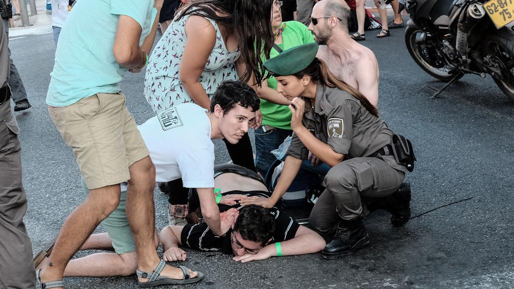 Lidé pomáhají jednomu ze zraněných