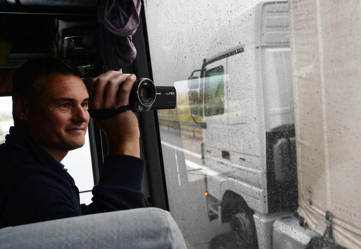 Policista kontroluje kamion z autobusu