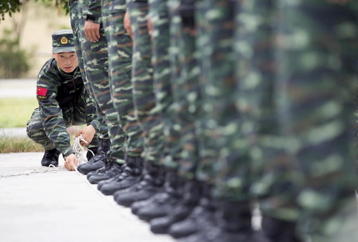 Voják čínské lidové armády zarovnává lanem ostatní vojáky během tréninku na přehlídku