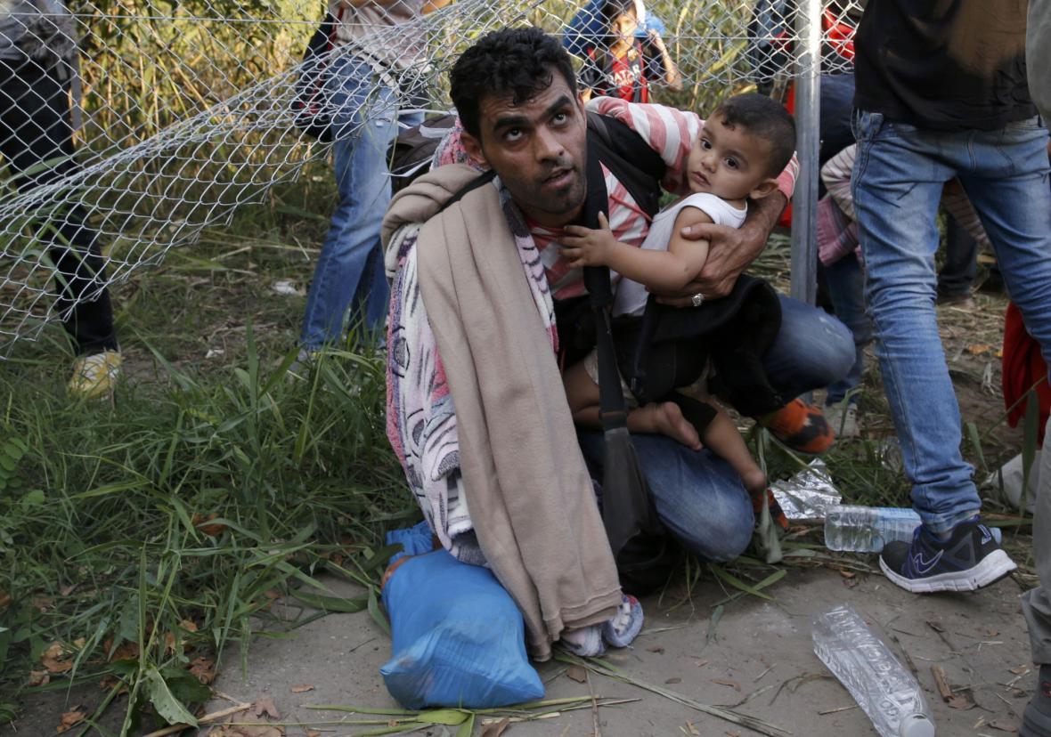 Uprchlíci překonávají plot na hranici Srbska a Maďarska
