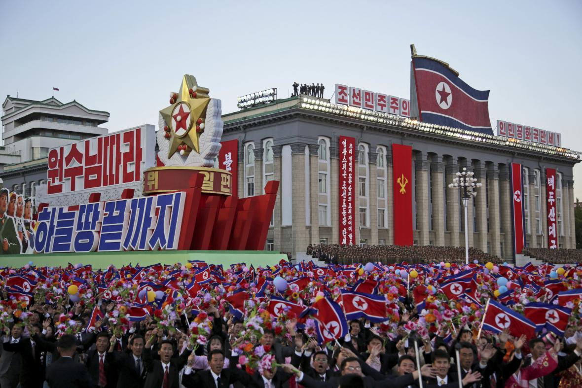 Severokorejci mávají vlajkami během přehlídky