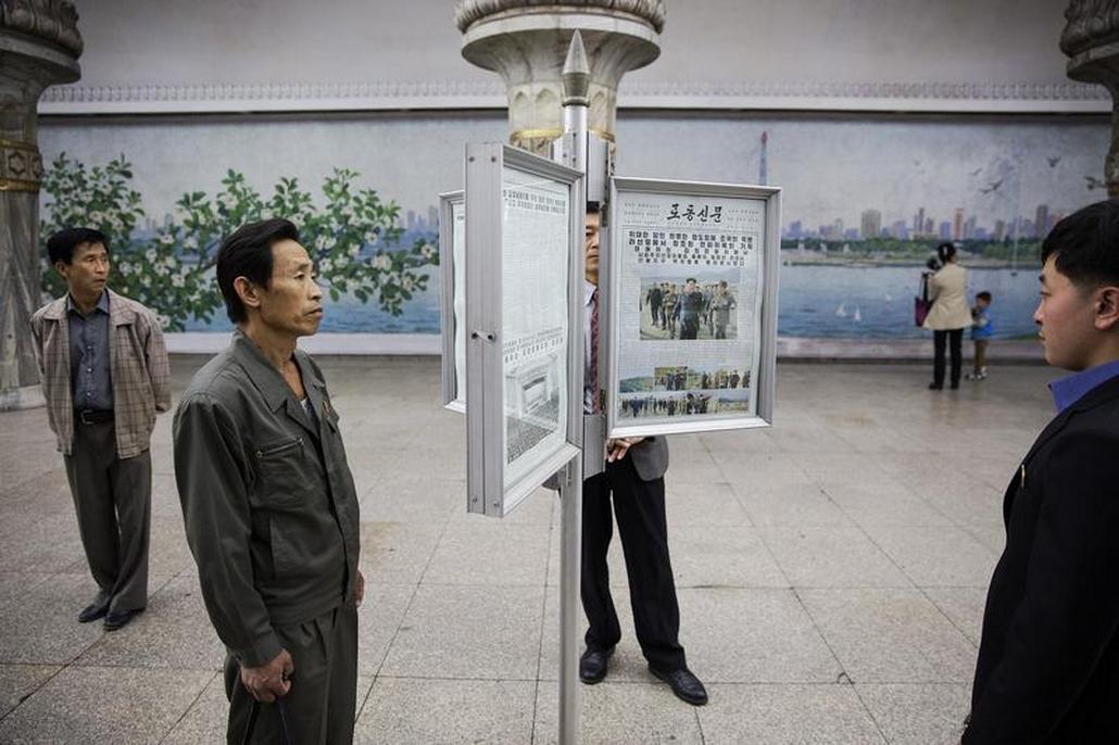 Lidé čtou zprávy na nádraží