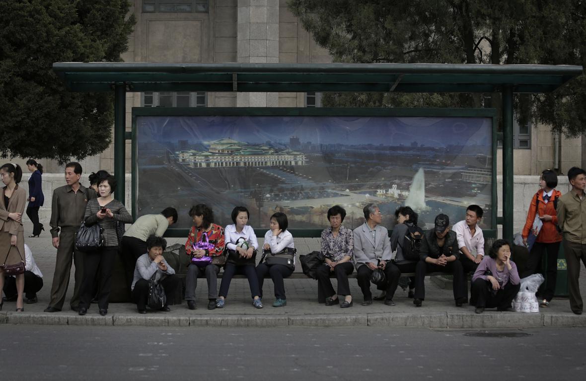 Cestující na zastávce autobusu