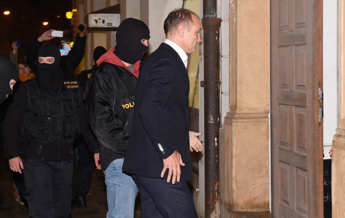 Policie vede zadrženého Ivana Langera do jeho domu v Olomouci