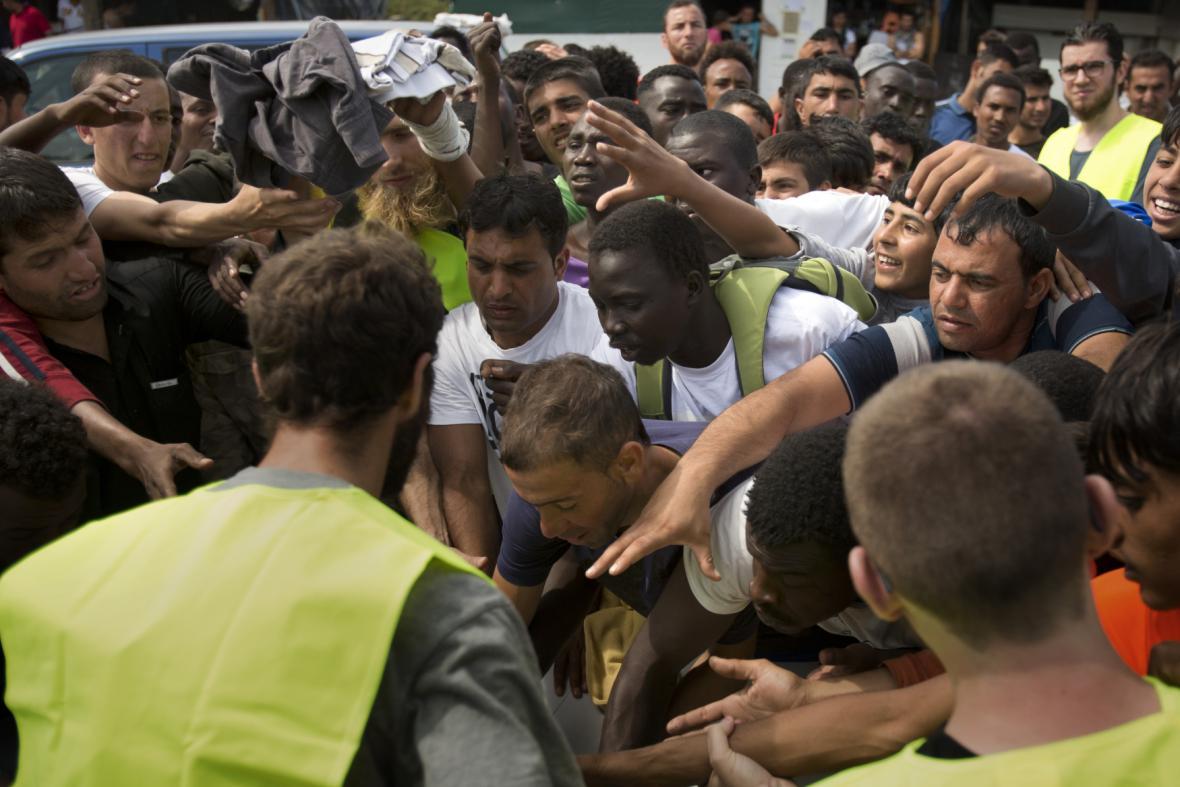 Lidé v táboře si rozebírají humanitární pomoc