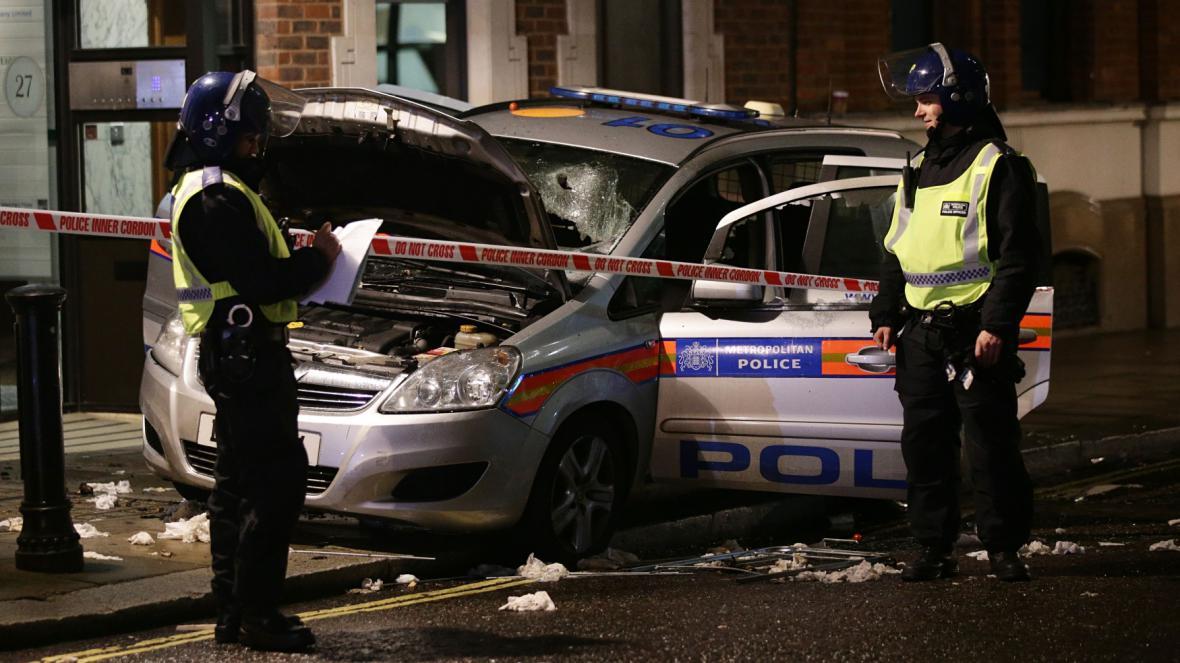 Zničené policejní auto na Million Mask March v Londýně