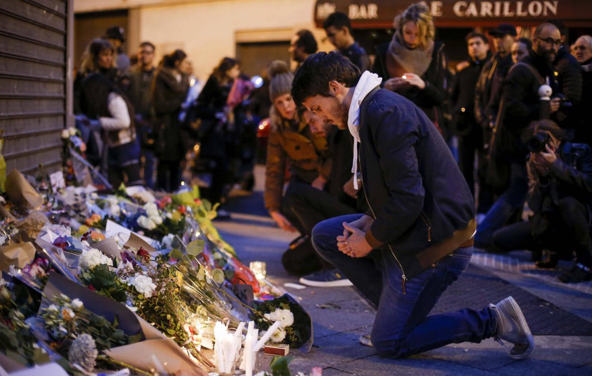 Lidé nosí květiny před restauraci, kde došlo k útoku