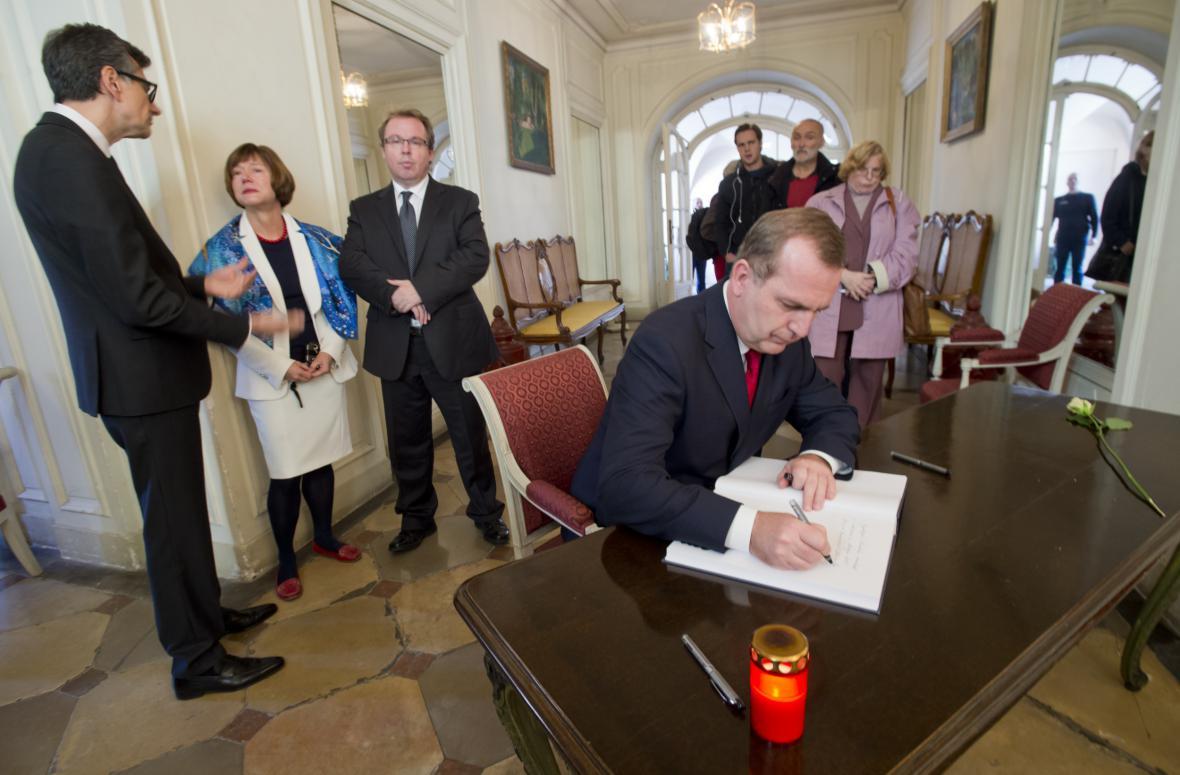 Rektor Univerzity Karlovy Tomáš Zima podepisuje kondolenční knihu na francouzské ambasádě v Praze
