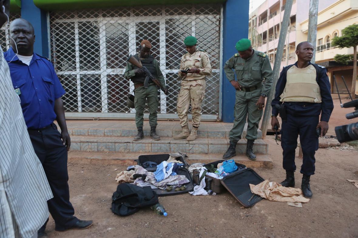 Malijští vojáci ukazují granáty a osobní věci atentátníků