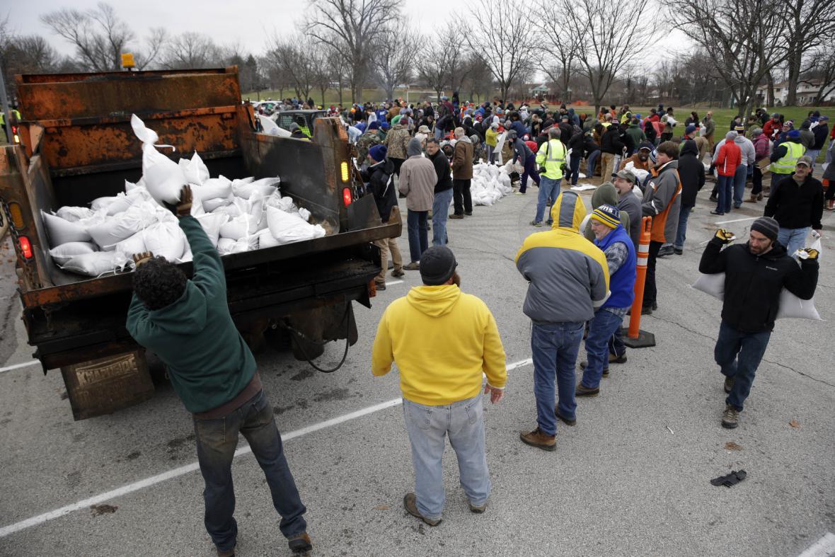 Dobrovolníci staví hráze z pytlů z pískem v St. Louis