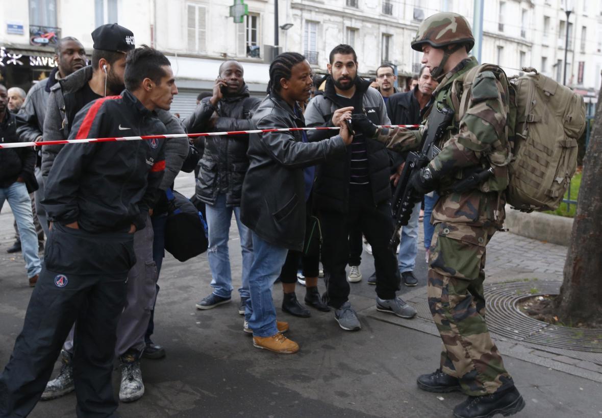 Policista legitimuje obyvatele Saint-Denis po razii v listopadu 2015