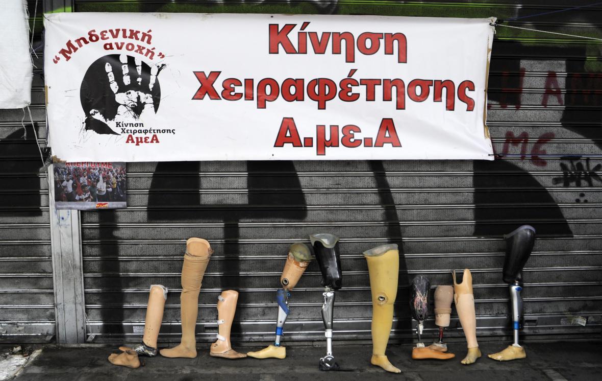"""Postižení Řekové umístili před ministerstvo práce prostetické končetiny a transparent: """"Hnutí za emancipaci lidí se zvláštními potřebami"""""""