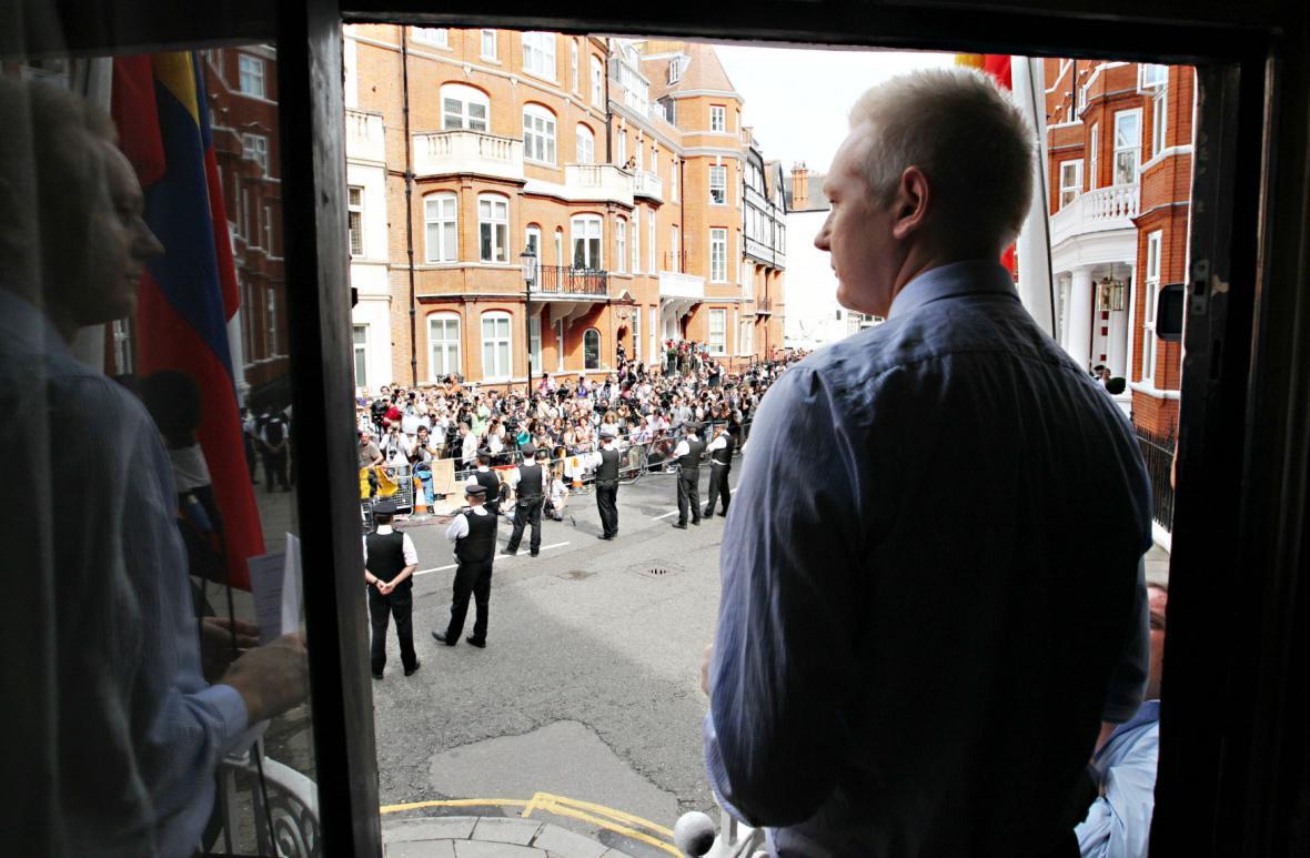 Julian Assange sleduje seskupené novináře před ambasádou