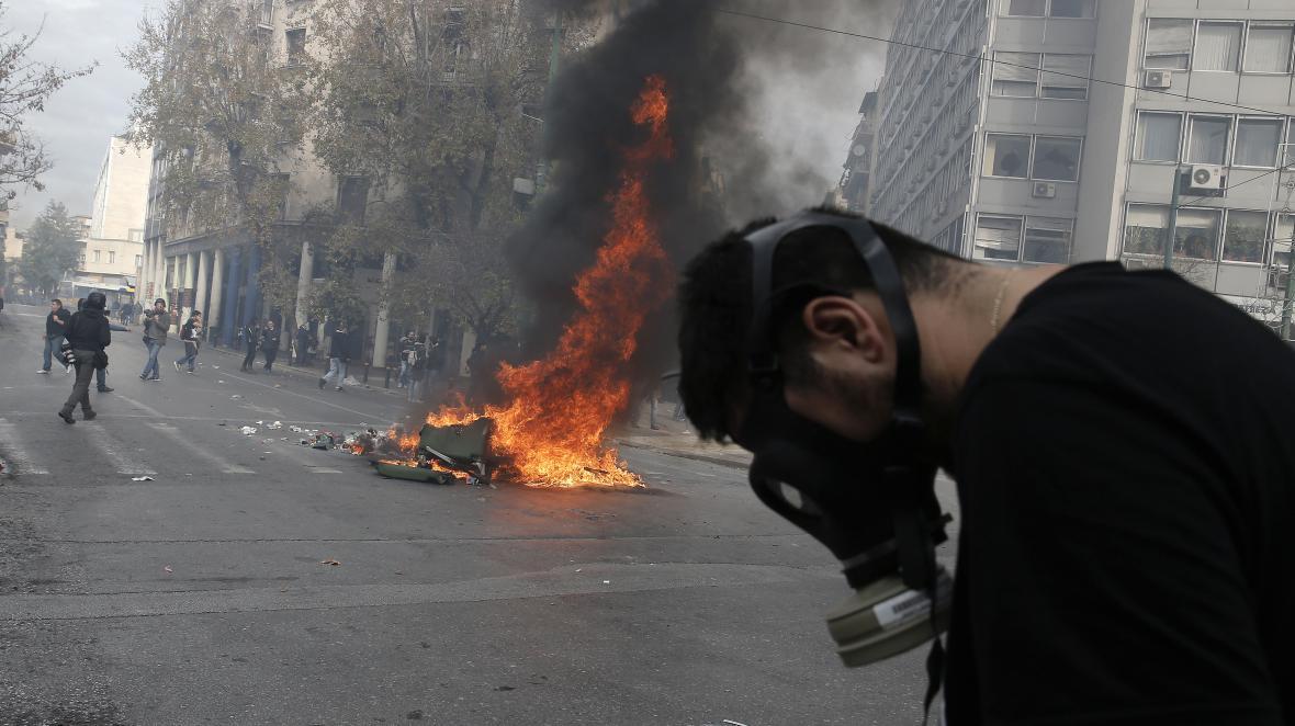Demonstrant před hořícím kontejnerem