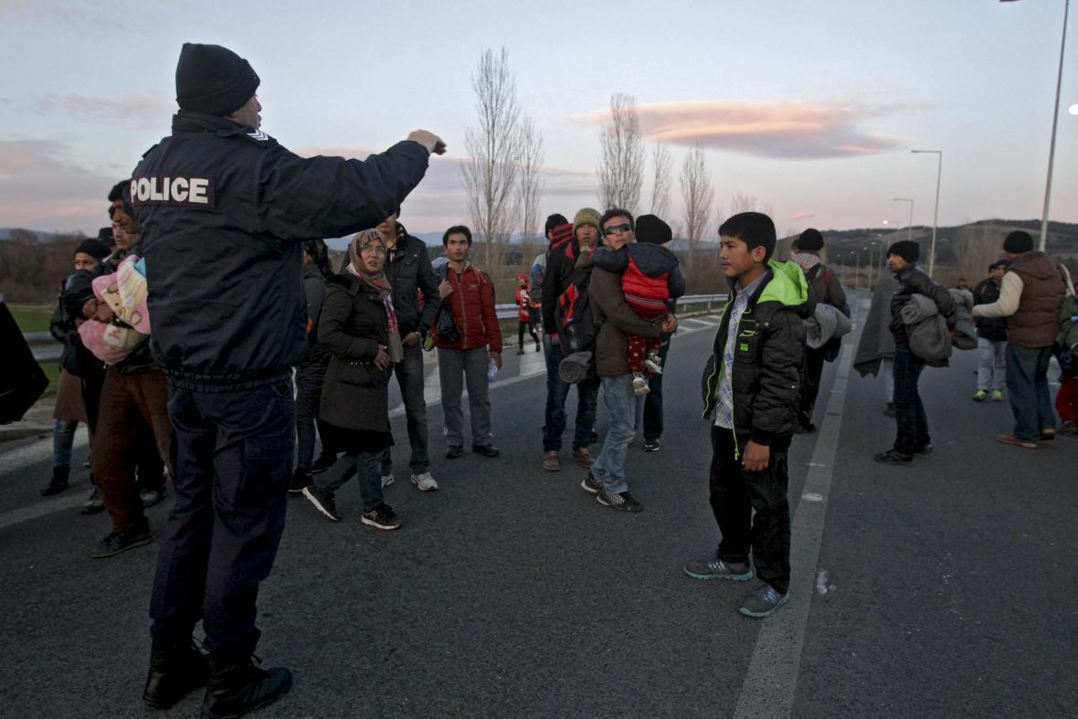 Řecký policista vykazuje od makedonských hranic migranty z Afghánistánu