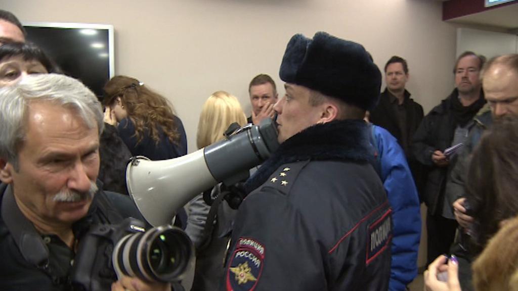 Policista žádá novináře, aby vyklidili sál