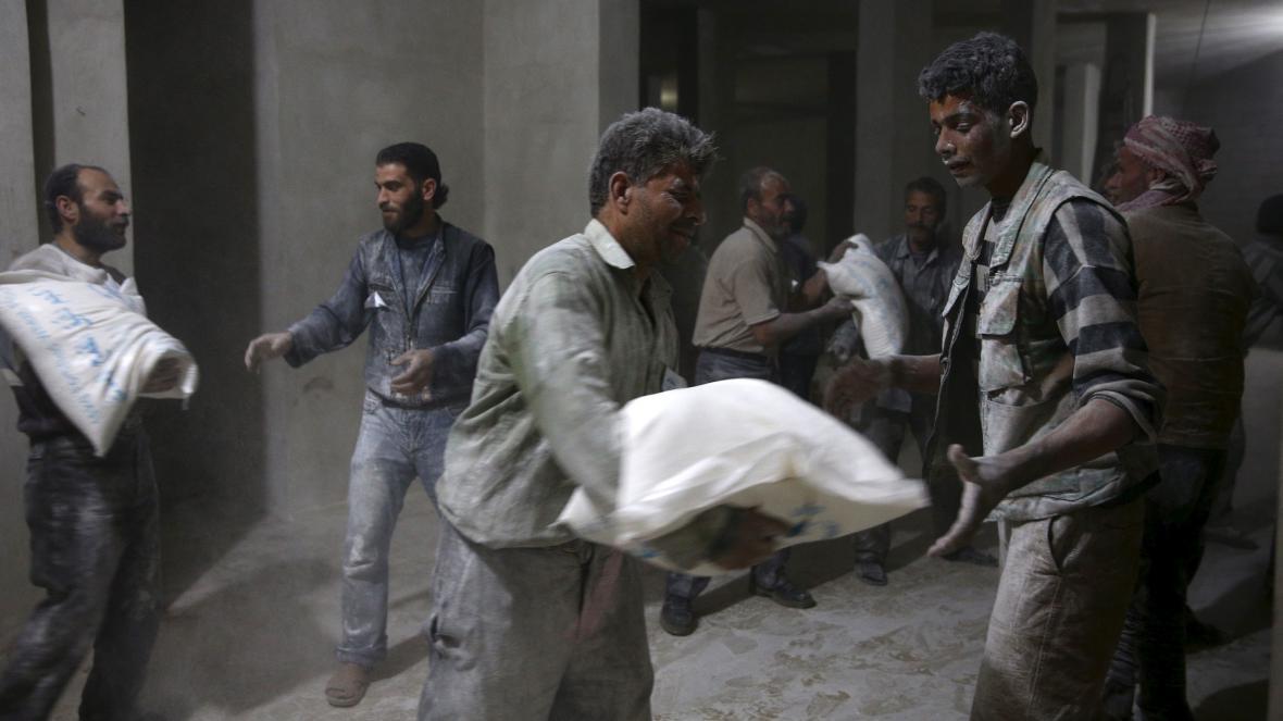 Muži vykládají mouku z konvoje Mezinárodního červeného kříže