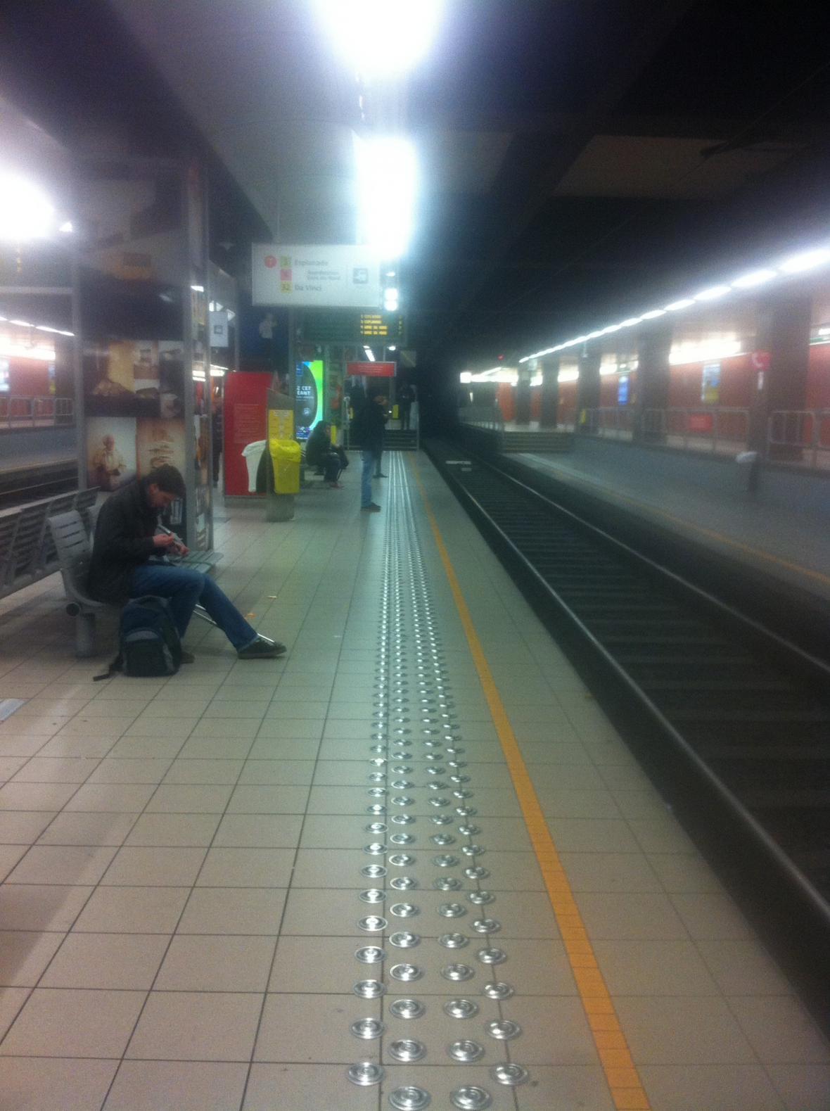 Poloprázdná stanice metra a všichni v ruce drží telefony