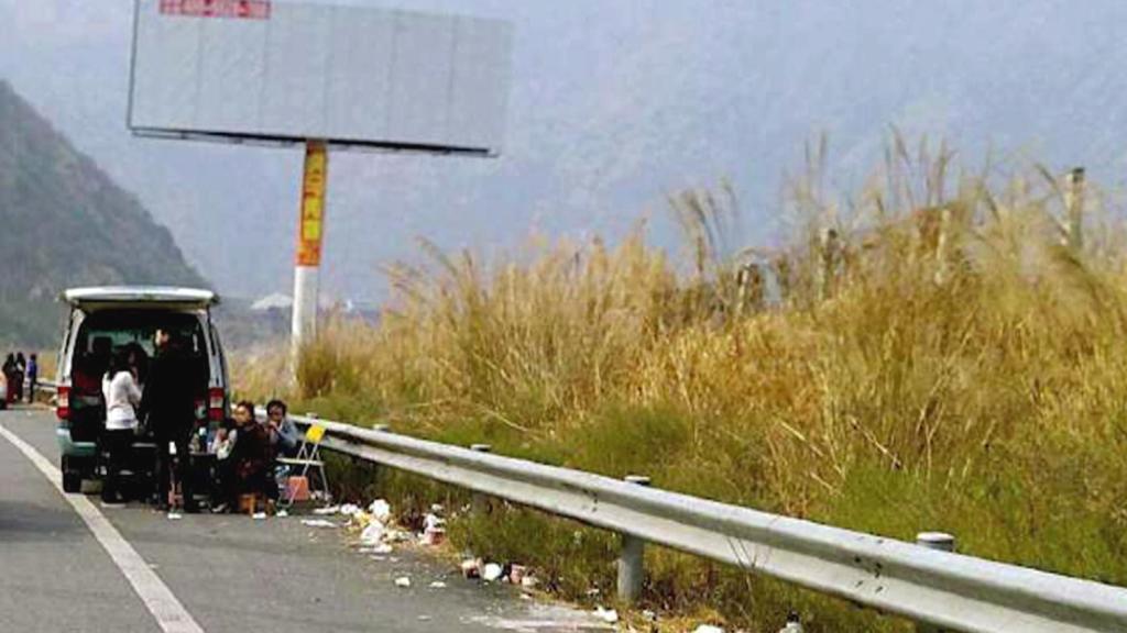 Čínská rodina piknikující na okraji dálnice