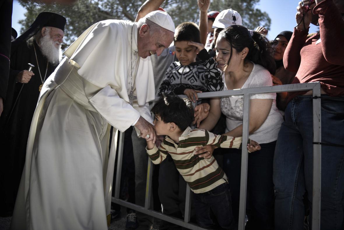Dítě líbá ruku papeže Františka na Lesbu