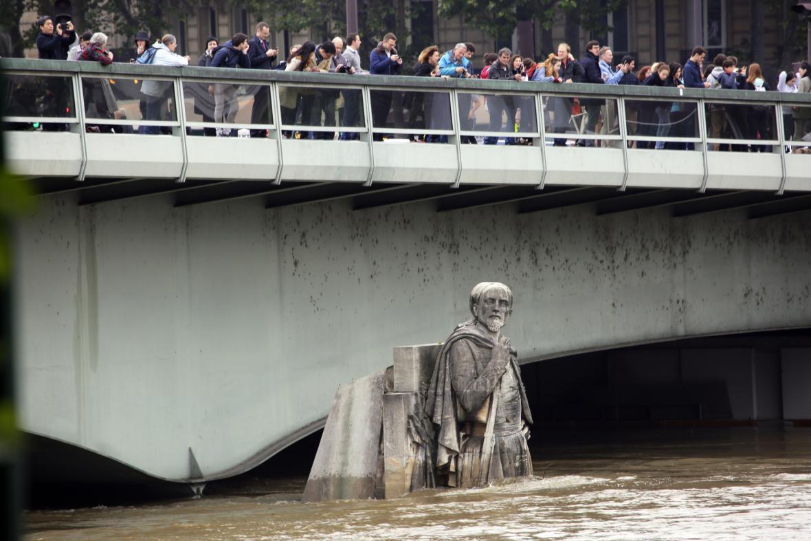 Lidé pozorují rozvodněnou Seinu z mostu Alma v Paříži