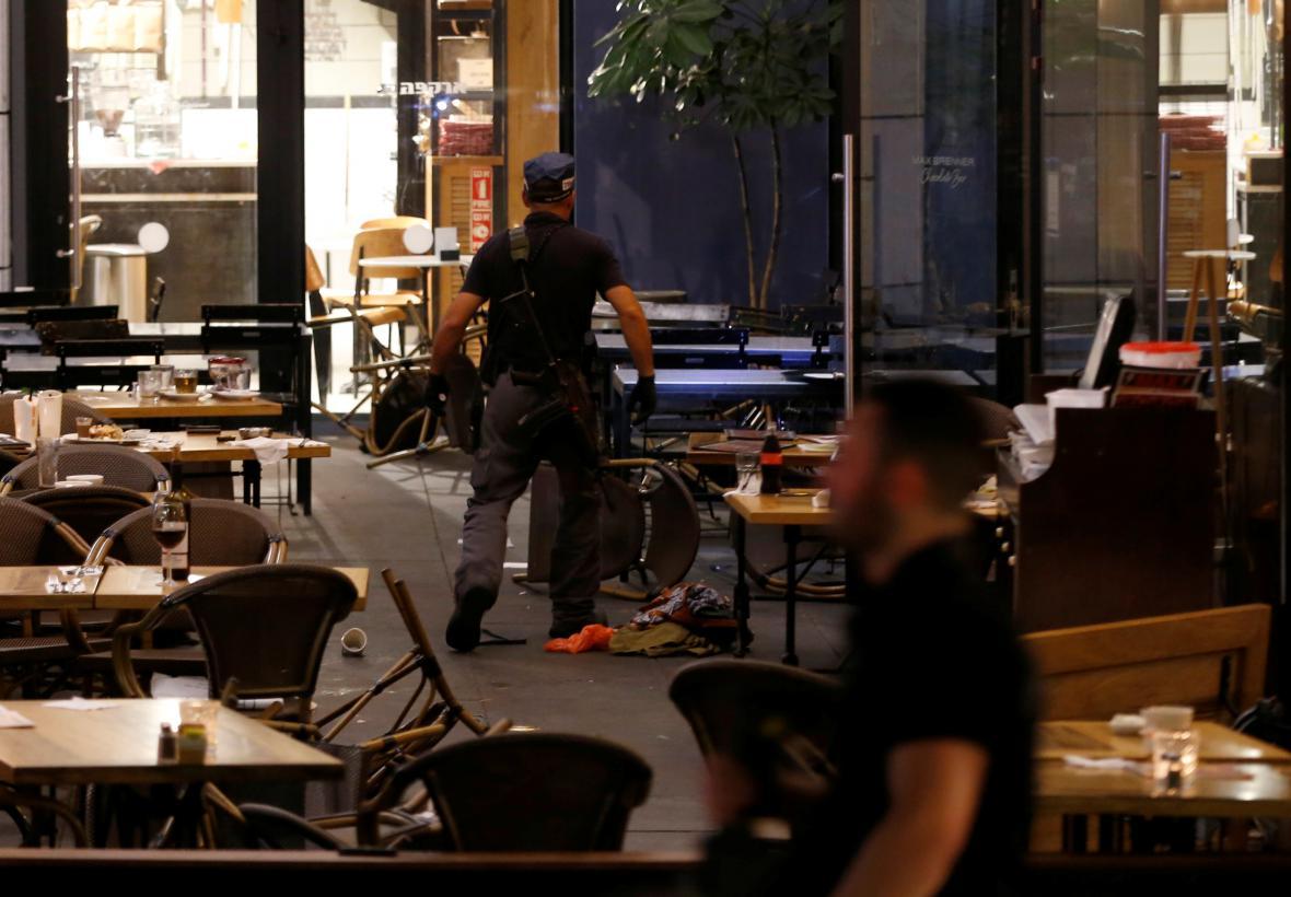 Izraelský policista prohledává restaurace po útoku