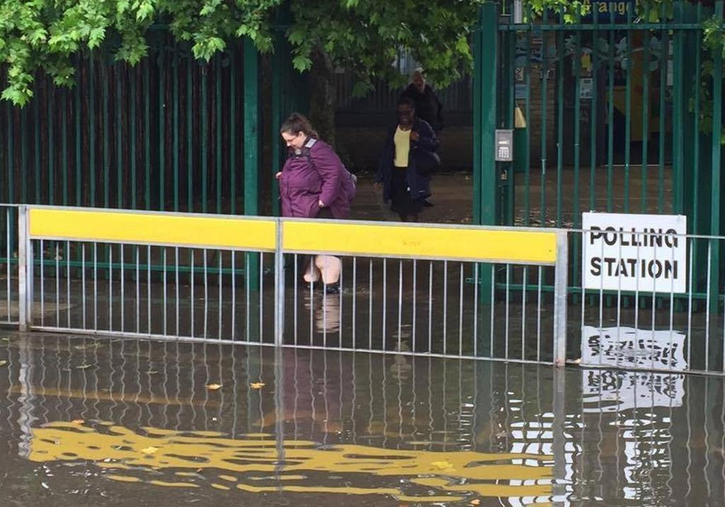 Žena se cestou z hlasování brodí po zaplaveném chodníku