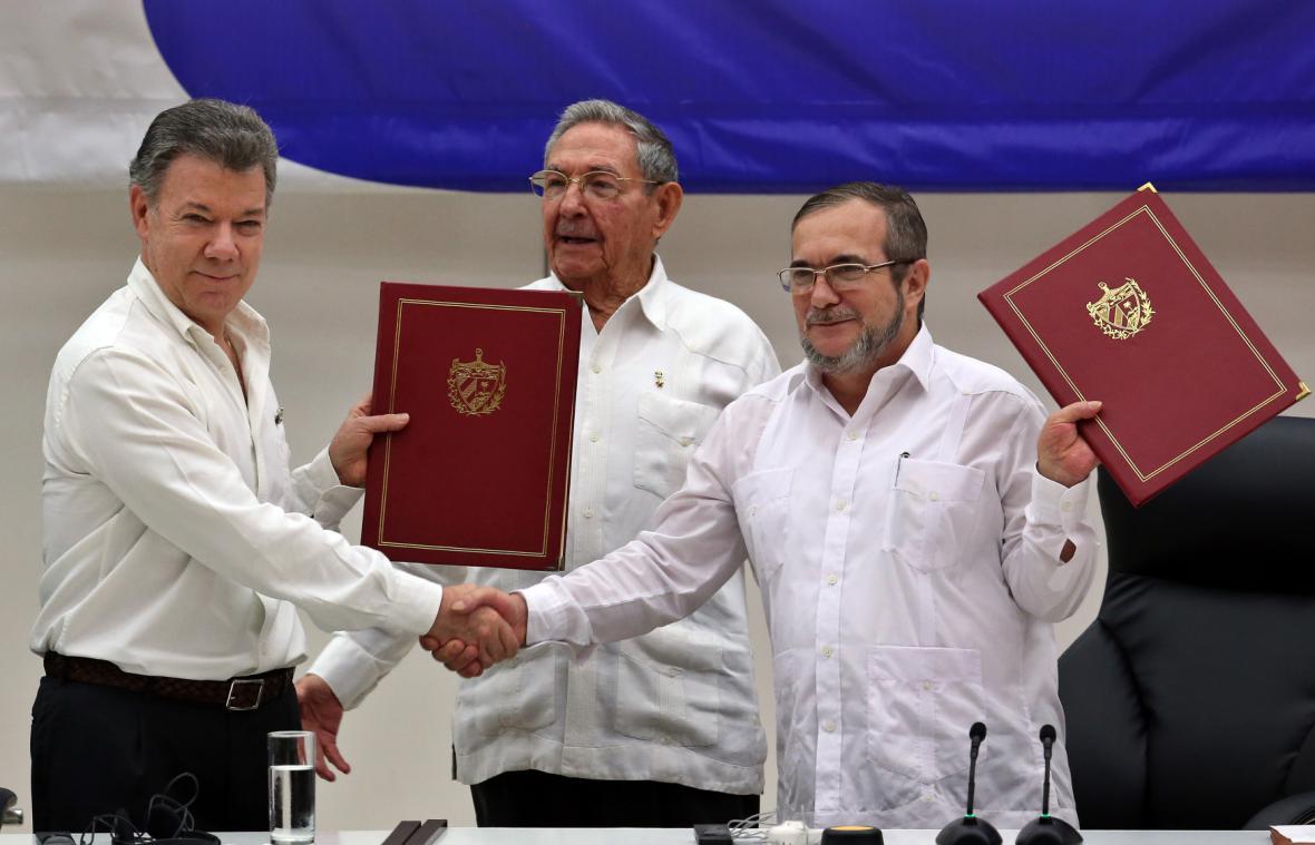 Mír podepsán. Kolumbijský prezident Juan Manuel Santos (vlevo) s velitelem povstalců Timoleónem Jiménezem (alias Timochenkem, vpravo). Přihlíží kubánský prezident Raúl Castro.